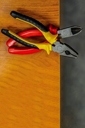 set pliers iron rubber handle pair black yellow red lower frame copy space wooden table