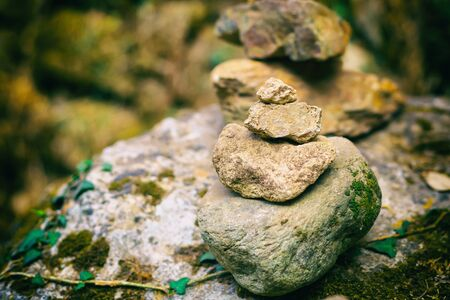vertical pile stones uneven close-up tower folded gray stone forest design