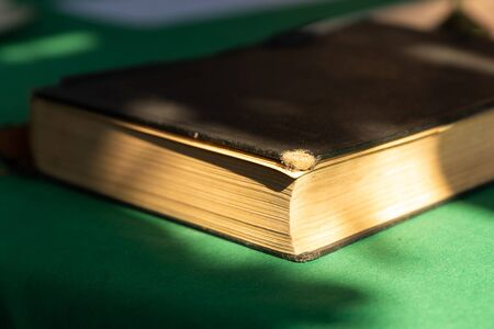 book in an old and weathered dark cover lies on a green cloth Stock Photo