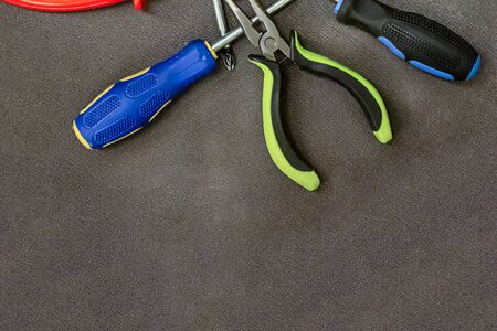 Tools for building a screwdriver and wire cutter lay a band on a brown background copy space