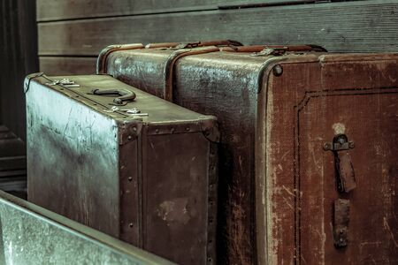 pair of dark brown suitcases stands upright, two luggage closeup vintage background