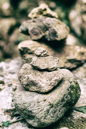 large vertical stone tower assembled from a small cobblestone set old weathered close-up