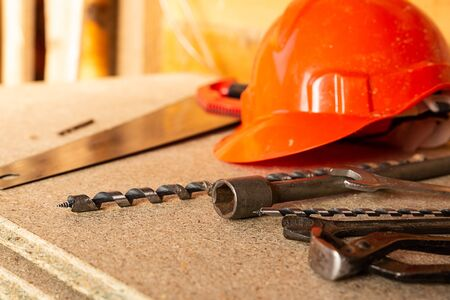 construction design pattern orange plastic helmet, set of drill drills and wire cutters lie on a light wooden background