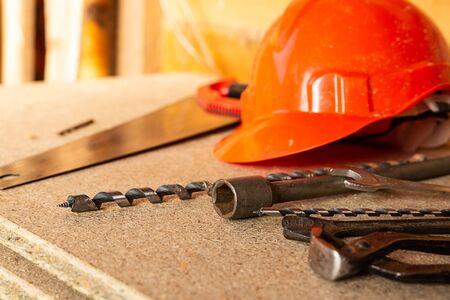 Konstruktionsmuster orangefarbener Plastikhelm, Bohrer und Drahtschneider liegen auf hellem Holzhintergrund