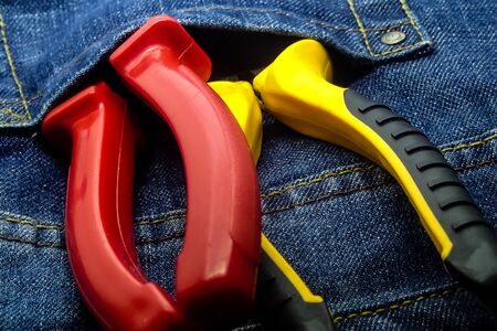 wire cutters with plastic handles red and yellow with black lie in the pocket of an electricians work clothes Stok Fotoğraf