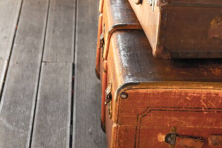 stack of old and weathered brown suitcases, a couple of luggage lie on the wooden floor of the railway station copy space