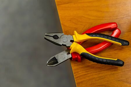 pair of plastic nippers with multi-colored handles lies on the edge of a wooden table Stok Fotoğraf