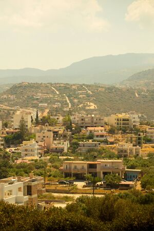 crete traditional city of greece white houses in a valley of mountains sunny afternoon vertical postcard