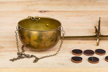 hanging scales old of bronze with a chain and coins runes on a table wooden background trade