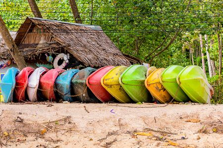 boat made of light plastic red, green, yellow and pink on a tropical island sandy beach
