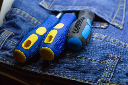 Screwdriver pair rubber handle in blue pocket jeans overalls. Repairman hand tools