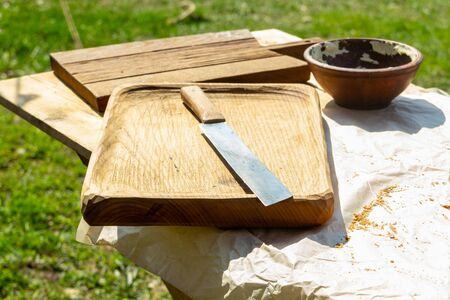 a large knife lies on a chopping board made of natural oak outdoor kitchen