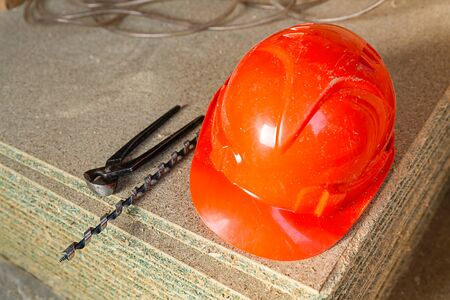 orange helmet to protect the worker, safety of work in construction, a long drill and pliers set engineering on wooden panels