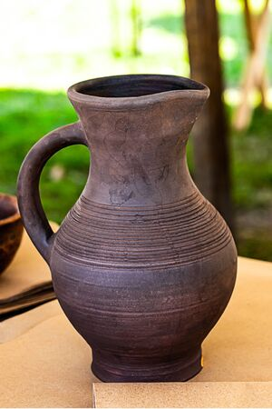 dark brown clay pot for storing milk stands on a wooden table