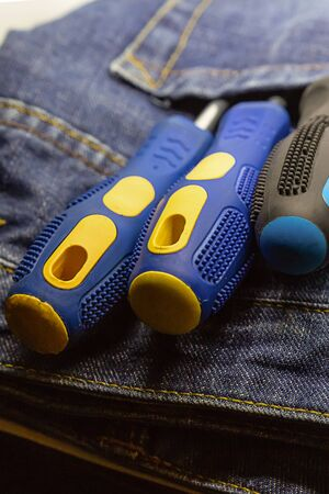 screwdriver pair blue fixation repair of electrical equipment blue denim background