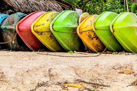 old colorful plastic boat green and yellow lies on the sandy beach of a tropical island