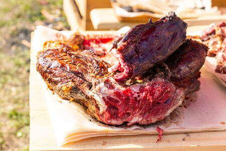 whole piece venison baked on an open fire fried rare lies on a wooden table