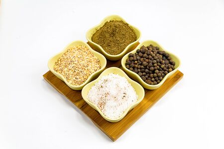 bowl of peppercorn, crushed dried garlic and cumin spice set on a wooden tray isolated background 版權商用圖片