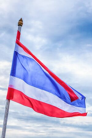 flag of Thailand with red, white and blue stripes against the sky