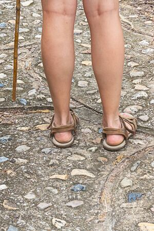 female legs in beige sandals, rear view, walk in the mountains vertical photo