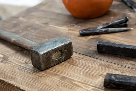 old rusty weathered hammer lies on the table on the background of tools