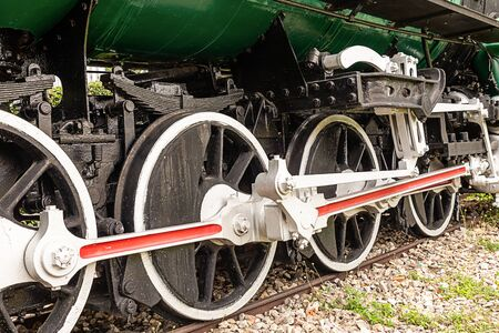 the wheels of the locomotive are large black with white rims standing in the tracks