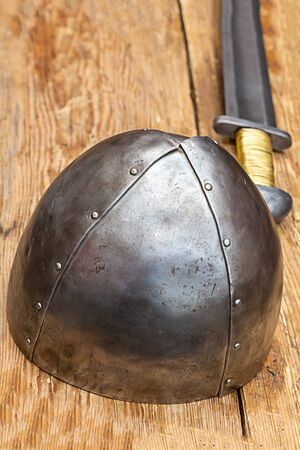 iron steel helmet stands on the background of a long sword on a wooden table Foto de archivo