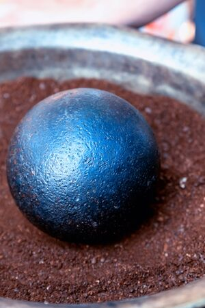 cannonball black and round close-up lies on a dark brown background