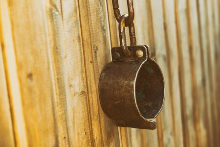 old handcuffs old traditional metal large hang on wooden stained background 版權商用圖片