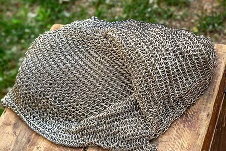 iron traditional chain mail lies in a pile on a wooden bench, rest on a halt