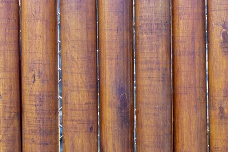 wooden fence made of thick tree trunks, vertical pattern dark brown