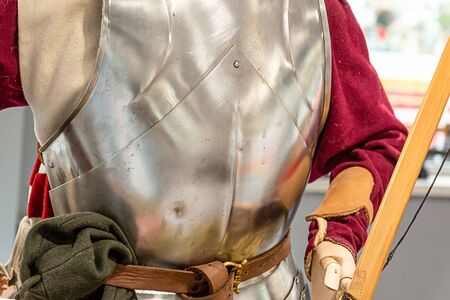 archer is dressed in an iron cuirass and a red shirt, military armor