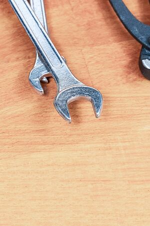 silver iron wrenches on a wooden background vertical photo