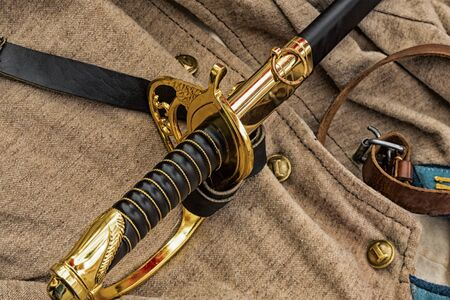 the sword is black the golden handle of the civil war of 1861-1865 lies against the background of the traditional soldier uniform, jacket and leather belt