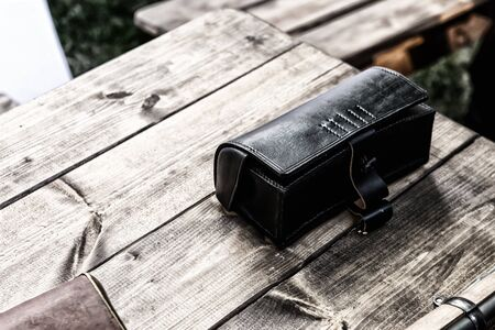 traditional leather cartridge belt in vintage style lies on a wooden table, toned photo