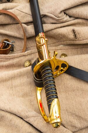 cavalry sword of the times of the civil war of 1861-1865, the black gold handle of the guardia against the background of a soldier's uniform