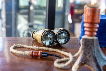 Vintage iron binoculars lies on a table close-up, a traditional way of navigating the sea