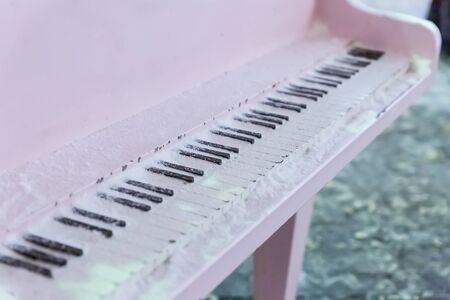 white piano with black and white keys covered with snow closeup