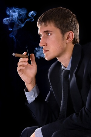 young smoking man with cigar on black background photo