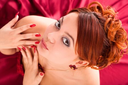 young attractive woman sitting in long red dress on red background. view from above. Stock Photo - 9357998