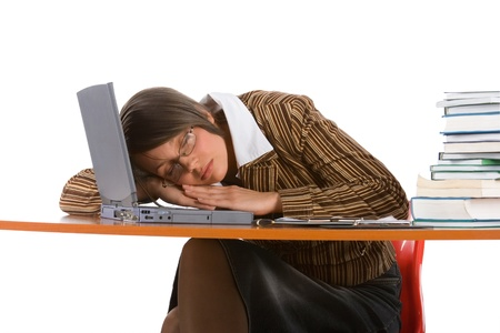 sleeping businesswoman with laptop and books at the table photo