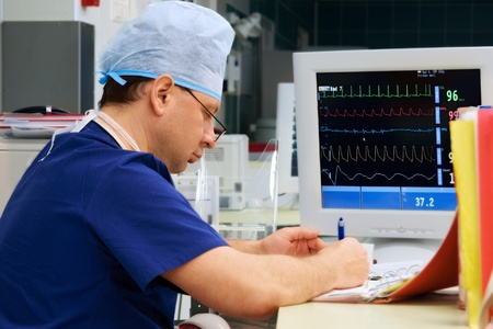 doctor in ICU writing prescription with monitor 免版税图像