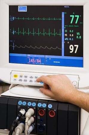 ekg: monitor with doctors hand in intensive care unit Stock Photo