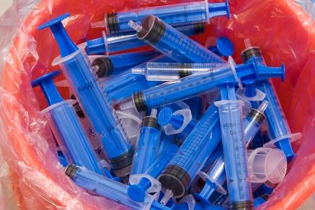 several syringes in recycle bin 免版税图像