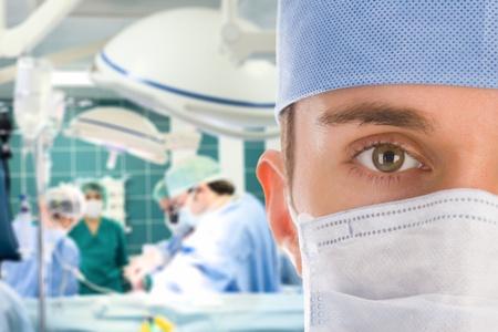 emergencia medica: Cirujano masculino con su equipo en la sala de operaci�n Foto de archivo