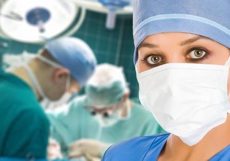 especialistas: Doctora en quir�fano con cirujanos en segundo plano