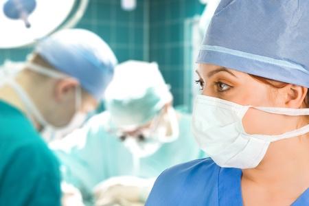 quirurgico: cirujano femenina con su equipo quir�rgico en segundo plano