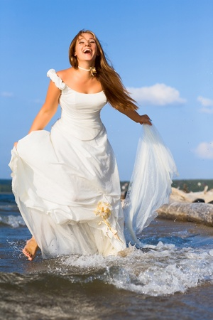 running laughing bride on the sea with blue sky on background