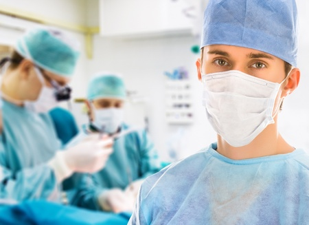 Male surgeon with two doctors on background in operation room photo