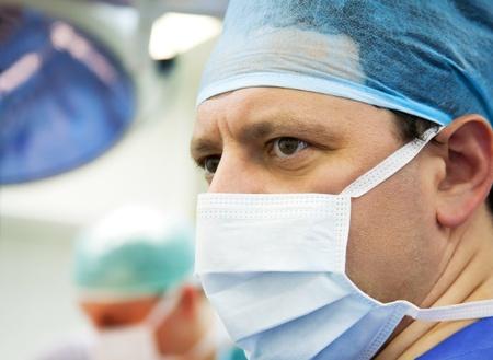 urgencias medicas: Mirar de cirujano masculino en la sala de operaci�n con su equipo Foto de archivo